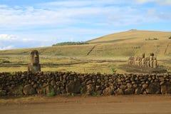 Odludny Moai blisko kamiennego ogrodzenia i sławni 15 Moai na platformie przy Ahu Tongariki, Wielkanocna wyspa Zdjęcia Royalty Free