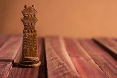 Odludny szachowy kawałek na nieociosanym stole z czerwonawymi brzmieniami zdjęcia royalty free