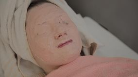 Odmłodnieć maskę na twarzy młoda dziewczyna w piękno salonie zdjęcie wideo