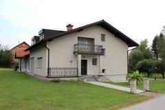 Odnawiący podmiejski rodzina dom z frontowym balkonem i kamieniem tafluje wejście otaczającego z świeżo ciącą zieloną trawą i mał obraz stock
