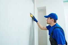 odnowienie Gipsiarza pracownik spackling ścianę z kitem zdjęcia royalty free