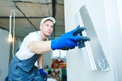 odnowienie Pracownik spackling ścianę z kitem obraz stock