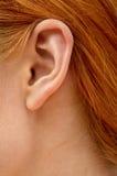 Oído de la señora del redhead Imágenes de archivo libres de regalías