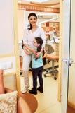 Odontología pediátrica La muchacha es feliz de encontrar con al dentista foto de archivo