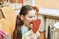 Odontología pediátrica La muchacha mira sus dientes en el espejo fotos de archivo libres de regalías