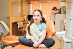 Odontología pediátrica Muchacha que se sienta en una silla dental foto de archivo