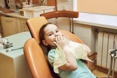 Odontologia pediatra A menina não quer tratar seus dentes imagens de stock royalty free