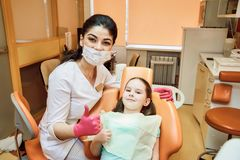Odontologia pediatra Olhar do dentista e da menina na câmera e no sorriso fotografia de stock