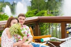 Odorare femminile di Youg fiorisce mentre si siede su un banco con un ragazzo fotografia stock libera da diritti