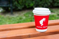 Julius Meinl coffee cup on a bench in the city park. stock photography