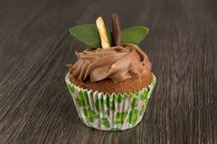 Odosobniona czekoladowa babeczka na ciemnym drewnianym stołowym tle z nowymi liśćmi zdjęcia royalty free