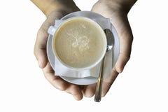 Odosobniona ręka trzyma Gorącą kawę Stawia szkło biel na bielu zdjęcie royalty free
