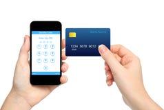 Odosobnione żeńskie ręki trzyma telefon i kredytową kartę i wchodzić do a Zdjęcie Stock