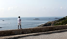 Odosobniony osoby odprowadzenie dalej nakrywa małą kamienną ścianę i morze śródziemnomorskie przy tłem w starej cytadeli Ibiza obrazy stock