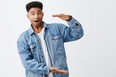 Odosobniony portret młody śmieszny ciemnoskóry mężczyzna z afro fryzurą w przypadkowej białej koszula pod drelichową kurtką Zdjęcie Stock