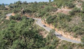Odosobniony samochodowy jeżdżenie w górę góry z wyginającą się drogą Obrazy Royalty Free