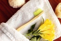 Odpady, biodegradable bambusowy toothbrush odkrywający w białym ręczniku z żółtym kwiatem obraz royalty free