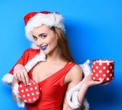 Odpakowanie prezenta seksowna niespodzianka Dziewczyny swimsuit i Santa chwyta bożych narodzeń prezenta czerwony kapeluszowy pude obrazy royalty free