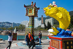 ODPARCIE zatoka, HONG KONG †'MARZEC 02, 2016: Ludzie podrzucają monetę w rybiego ` s usta wierzący ja szczęście MARZEC 02, 2016 Obraz Royalty Free