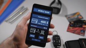 Odpierająca zapłata przez mobilnego bankowości zastosowania na smartphone Mężczyzna przenosi pieniądze od jego kredytowej karty i zdjęcie wideo