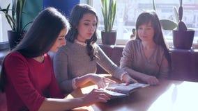 Odpoczywa przy kawiarnią, przyjaciele wybiera łasowanie od menu obsiadania przy stołem zbiory wideo