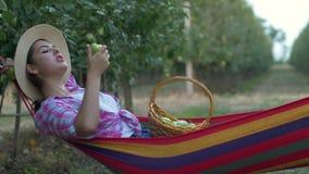 Odpoczywa w ogródzie i je jabłka na naturze podczas zbierać, szczęśliwi dziewczyn kłamstwa w hamaku zbiory wideo