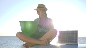 Odpoczywa, zabawy dziewczyna siedzi na dachowym retro samochodzie z słoneczną baterią i laptopem w rękach outdoors, młodej kobiet zbiory