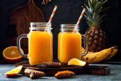 Odporny reklamiarstwo, anty podżegający smoothie z pomarańcze, ananas, turmeric Detox ranku soku napój fotografia royalty free