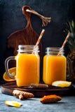 Odporny reklamiarstwo, anty podżegający smoothie z pomarańcze, ananas, turmeric Detox ranku soku napój zdjęcia stock