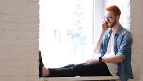 Odpowiadanie rozmowa telefonicza, rozmowa projektantem, Siedzi w okno, Czerwonych Hairs i brodzie, fotografia stock