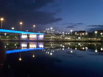 Illuminated bridge over a calm river in late evening royalty free stock photos
