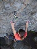 Odważna dziewczyna wspina się up na niebezpiecznych skałach Zdjęcia Stock