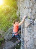 Odważna dziewczyna wspina się up na niebezpiecznych skałach Zdjęcie Stock