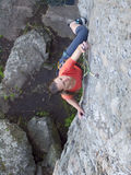 Odważna dziewczyna wspina się up na niebezpiecznych skałach Fotografia Stock