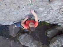 Odważna dziewczyna wspina się up na niebezpiecznych skałach Obraz Royalty Free