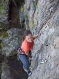 Odważna dziewczyna wspina się up na niebezpiecznych skałach Zdjęcia Royalty Free