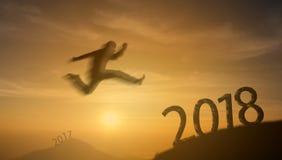 2018 odważnego mężczyzna pomyślny pojęcie, sylwetka mężczyzna skacze nad th Fotografia Royalty Free