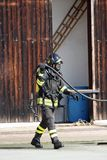 Odważni strażacy z zbiornikiem tlenu podpalają podczas ćwiczenia trzymającego obrazy royalty free