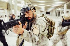 Odważny i poważny żołnierz stoi z jego combads w jaskrawym i błyszczącym długim pokoju Brodaty facet bierze cel podczas gdy fotografia royalty free