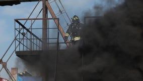 Odważny strażak iść w dół drabina w ogieniu zbiory
