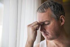 Odważny wieka średniego mężczyzna patrzeje nadokiennego, Smutnego i przygnębionego biznesmena samodzielnego, fotografia royalty free
