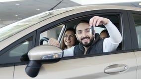 Odwiedzać przedstawicielstwa firmy samochodowej Piękna rodzina jest opowiadająca i uśmiechnięta podczas gdy siedzący w ich nowym  zbiory