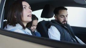 Odwiedzać przedstawicielstwa firmy samochodowej Piękna rodzina jest opowiadająca i uśmiechnięta podczas gdy siedzący w ich nowym  zdjęcie wideo