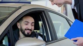 Odwiedza sala wystawową Młody człowiek siedzi w jego nowym samochodzie dostaje chwytowi samochodowych klucze patrzeje kamerę i on zbiory