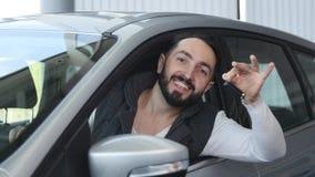 Odwiedza sala wystawową Młody człowiek siedzi w jego nowym samochodzie dostaje chwytowi samochodowych klucze patrzeje kamerę i on zdjęcie wideo