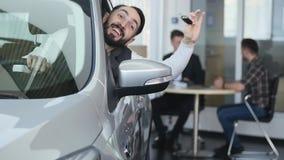 Odwiedza sala wystawową Młody człowiek siedzi w jego nowym samochodzie dostaje chwytowi samochodowych klucze patrzeje kamerę i on zbiory wideo