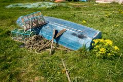 Odwrócona wioślarska łódź w polu z homarów wiosłami i garnkami obrazy stock
