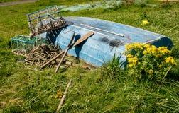 Odwrócona wioślarska łódź w polu z homarów wiosłami i garnkami zdjęcie royalty free