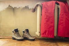 Odzieżowy obwieszenie na ciepłym starym grzejniku, obok którego stoi buty fotografia royalty free