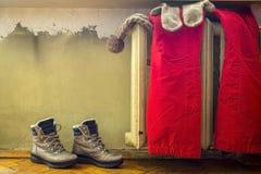 Odzieżowy obwieszenie na ciepłym starym grzejniku, obok którego kują stojaki obrazy stock